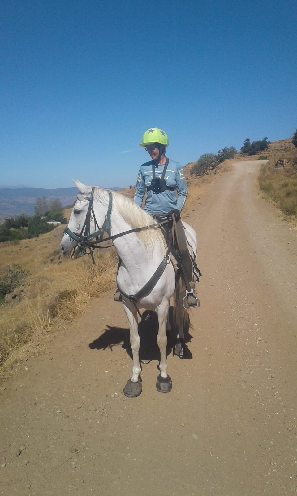 Me riding a grey horse, Piper, out on the sierra