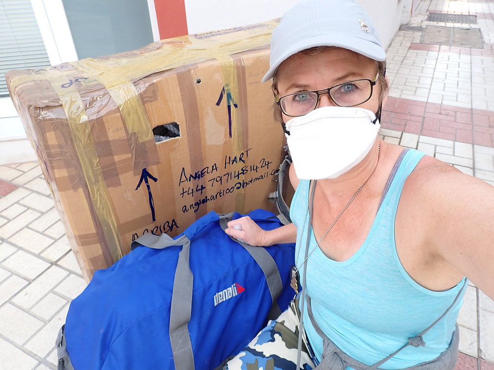 Me outside the hostal with my luggage, wearing a face mask