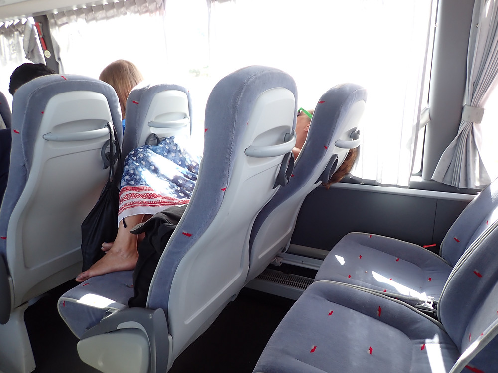 Inside the bus, a woman lays on the seat and does wear a mask