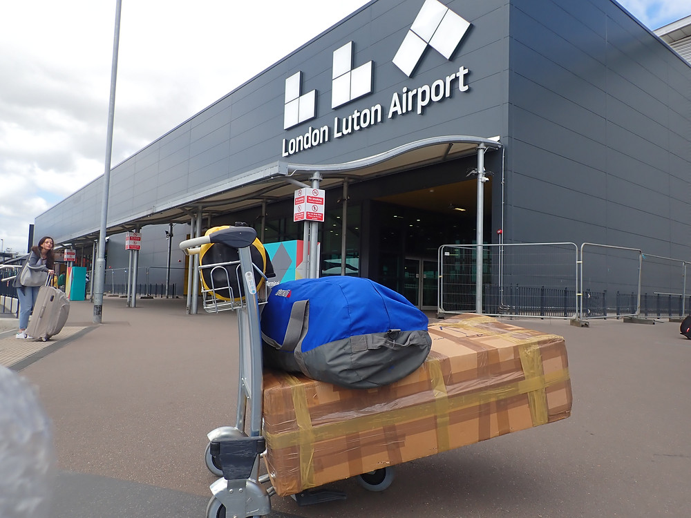 My luggage on a trolley outside the Luton Airport terminal