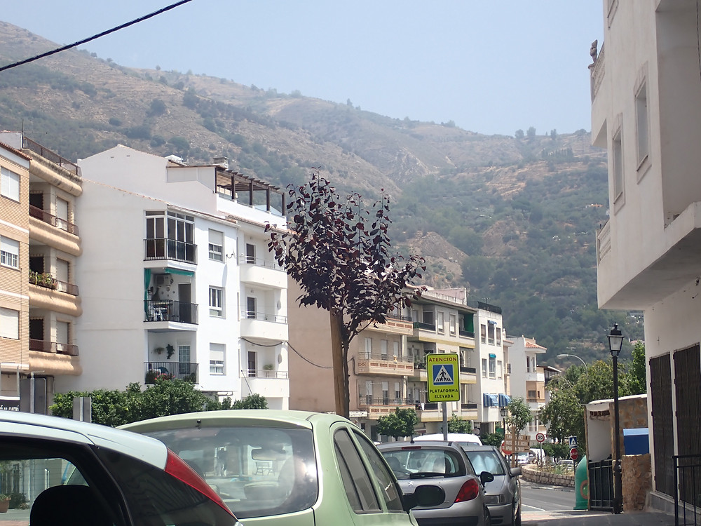 A street with buildings, cars and mountains in the distance