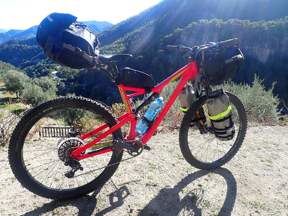 Mountain bike with bikepacking gear fitted in the foreground with mountains in the background