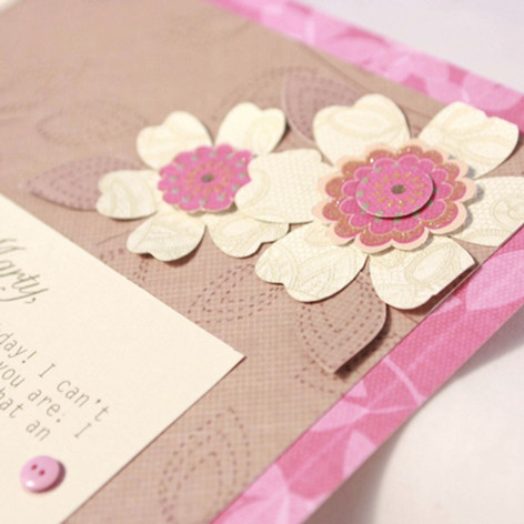 A close up of hand cut flowers on a 70th birthday scrapbook page
