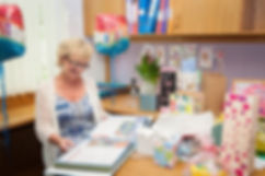 Headmistress is sittng downlooking through a scrabok album from he pupils and staff. She is surrunded by ballons gifts and flowers