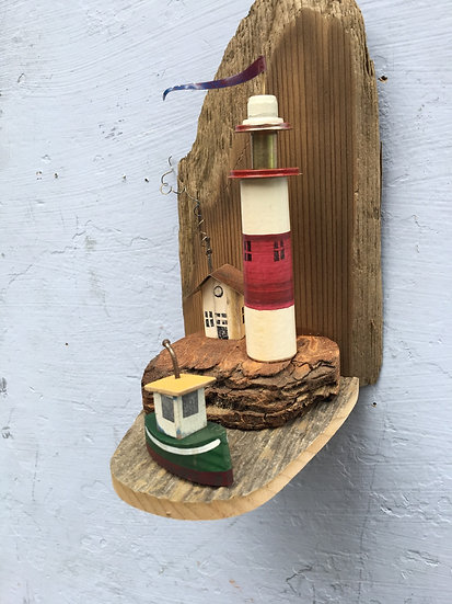 mini lighthouse with green boat