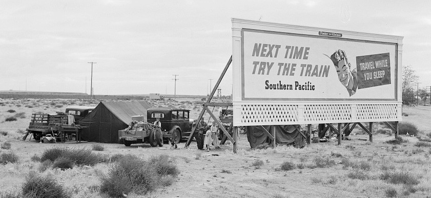 dust bowl families camping under shade of billboard