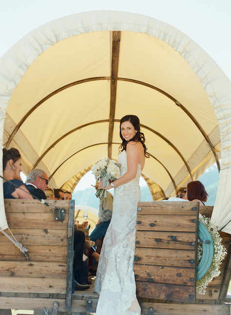 Bride Smiling on the Back of a White Canvas Covered Wagon