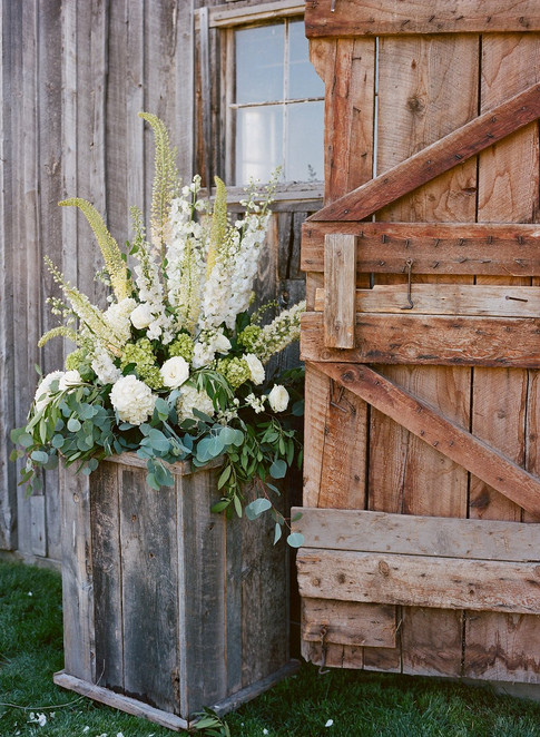 Large White and Green Flower Arrangement in a Wooden Box propping open a Wooden Barn Door