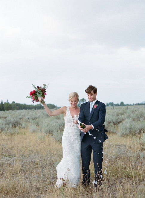 Bride and Groom Walking in a Field with a Champagne Bottle Popping