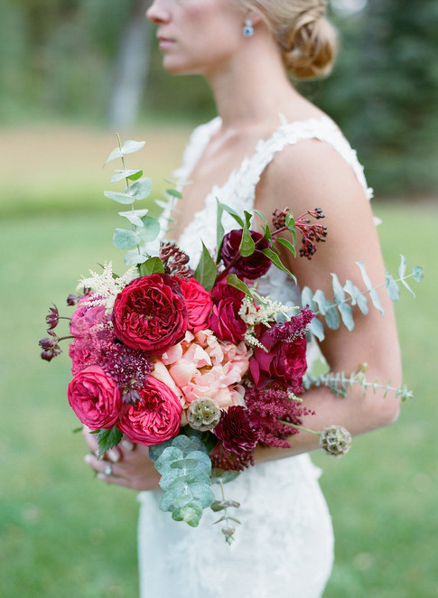 Bride Turned to the Side Holiding a Pink and Burgundy Wedding Bouquet