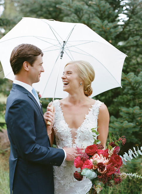 Bride and Groom Standing under a White Umbrella Smiling at Eachother