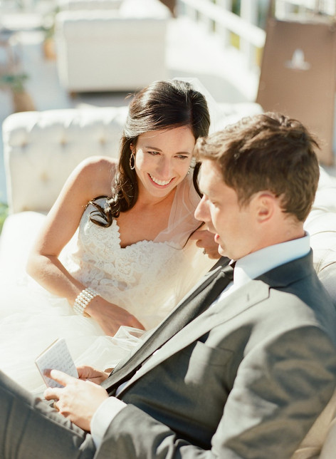 Bride and Groom Laughing on a White Chesterfield Sofa