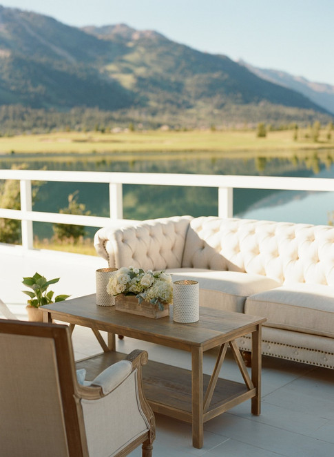 Cream Chesterfield Sofa and Wood coffee Table on a Deck in front of a Lake