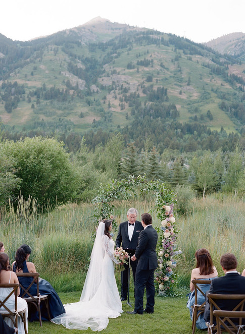 Bride and Groom in front of Wedding Flower Arch in the Mountains