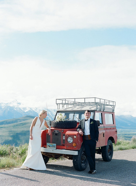 Bride and Groom Standing in Front of an Old Red Land Rover on a Mountainside