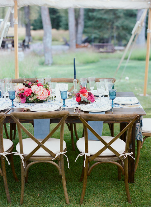 Wooden Table with Blue Tablesetting, Pink Flowers and Wooden Crossbacked Cafe Chairs
