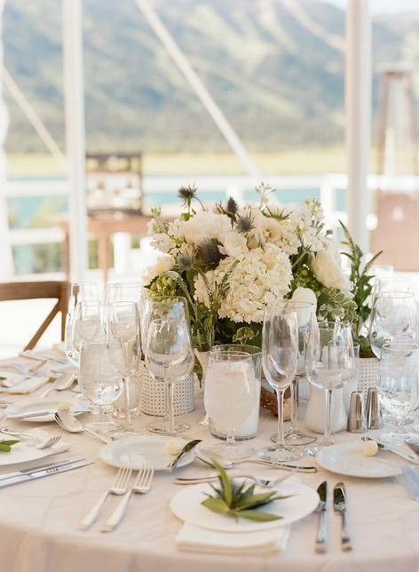 Round Table with Light Grey Linen, White and Silver Tablesettings and White and Green Flowers in fron of a Lake