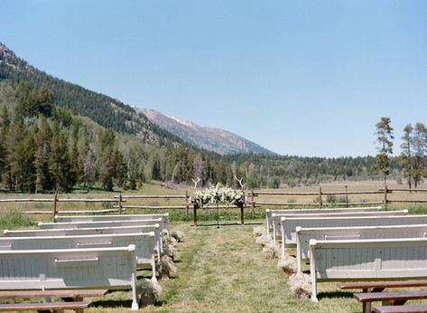 Field with Empty White Wooden Benches Lined Up for a Wedding Ceremony