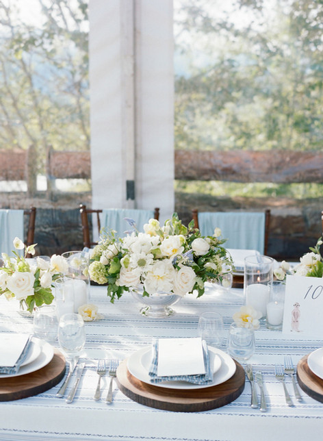 Wood and White Tablesetting with White and Green Flowers in a Silver Bowl