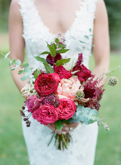 Bride holding a Bridal Bouquet with Pink and Burgundy Roses, Pink Peonies, and Eucalyptus