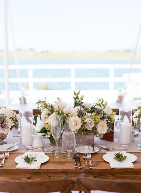 Wooden Table with White and Green Flowers and Candles in front of a Lake
