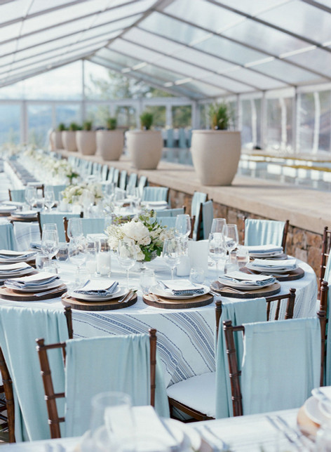 Large Clear Tent with a Round Table Set with Light Blue Striped Linens and Wood Accents