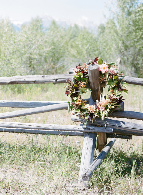 Green and Pink Flower Wreath Hanging on a Wooden Fence