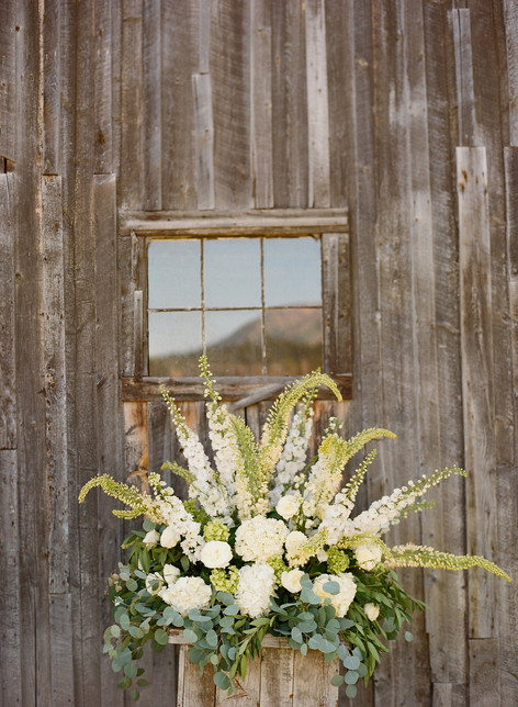 Large White and Green Flower Arrangement in a Wooden Box against a Wooden Barn