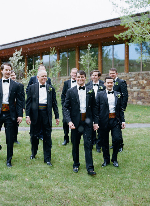 Groom and Groomsmen walking on Grass with Snow Falling