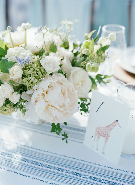 White Peony in a Flower Arrangment next to a Table Number card with a Giraffe and the number 1