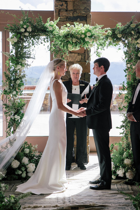Bride and Groom Face Eachother Holding Hands under Wedding Arch