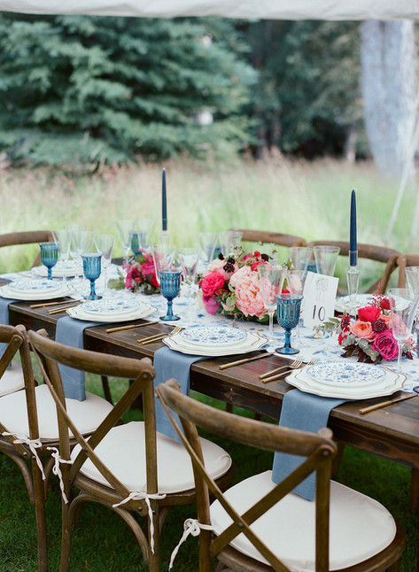 Wooden Table with Blue Plates and Napkins and Bright Pink Flowers