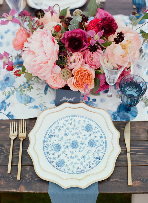Tablesetting with Gold Scalloped Charger, Blue Flower Patterned China, Gold Flatware, Blue Glassware and Bright Pink Flowers