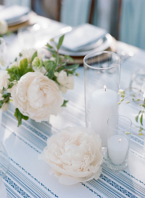 Large White Peony Laying on a Light Blue Striped Linen with Candlelight