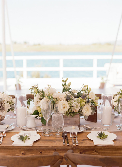 Long Wooden Table with White and Green Flowers in a Wooden Box on a Light Grey Table Runner in front of a Lake