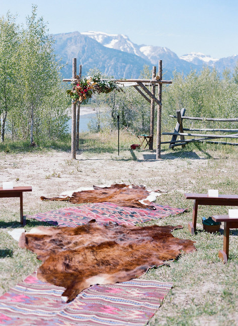 Cowhide Rugs Lining Aisle to the Aspen Wood Wedding Chuppa