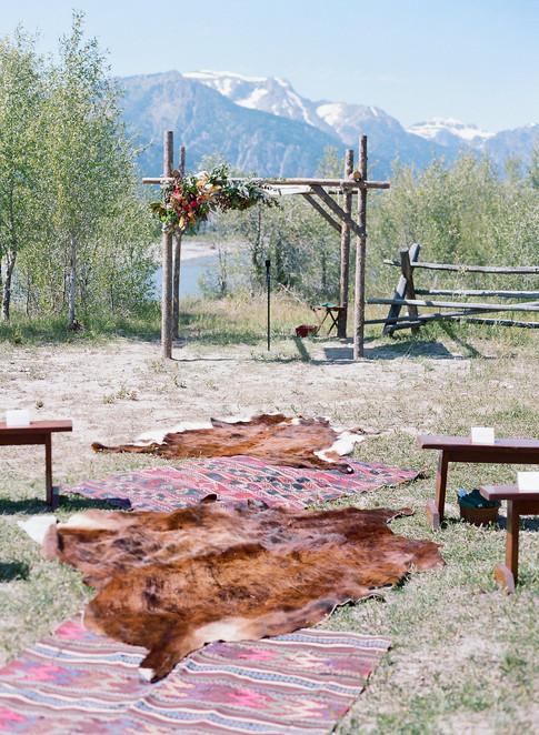 Cowhide Rugs Lining Aisle to the Aspen Wood Wedding Chuppa