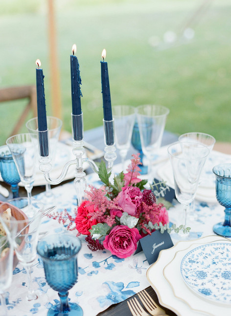 Pink Flowers on a Blue Patterned Table Runner with Three tall Blue Candlesticks Lit