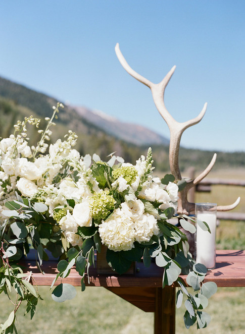 White and Green Flower Arrangement on Wooden Table with Antlers Behind it
