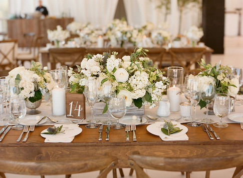 Tablescape with White and Green Flowers on a Light Grey Table Runner, Silver Flatware and Candles