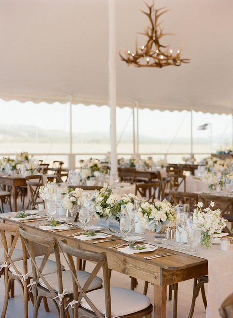 White Tent with Rustic Wooden Tables and Antler Chandelier