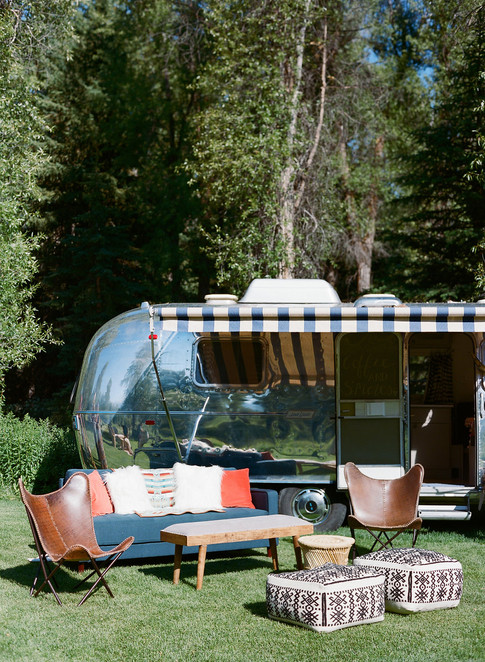 Couch and Leather Chairs in front of Silver Airstream Bar
