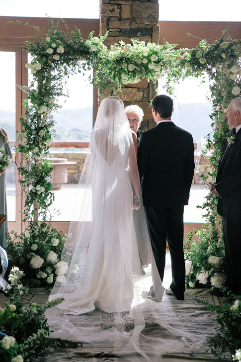 Bride and Groom underneath a Wedding Arch with wild Greenery and White Roses and Peonies