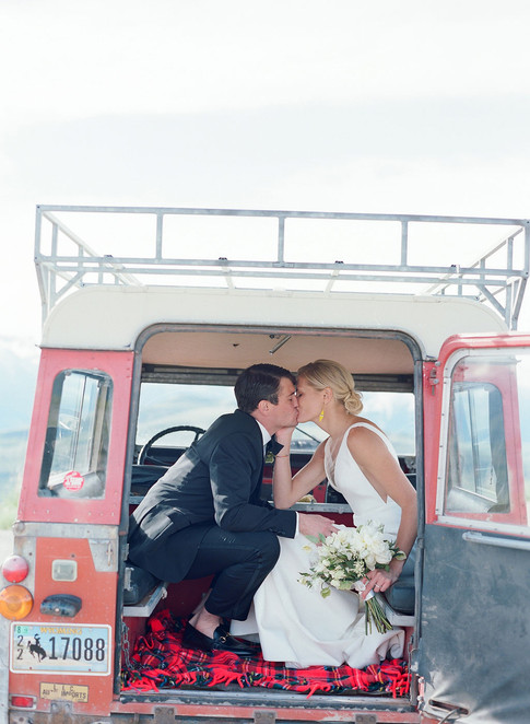 Bride and Groom Kissing in an Old Red Land Rover