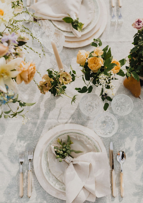 Dreamy Tablesetting with Cream Napkins Arranged with Green Berries, Woven Straw Silverware, Three Crystal Glasses and Small Vases with Yellow Roses