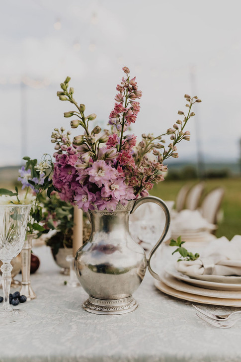 Purple Delphinium in a Vintage Silver Pitcher on a Table