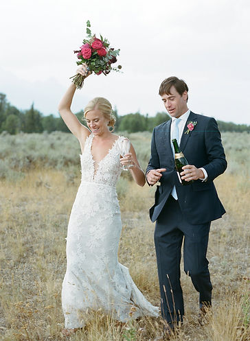 Bride and Groom Walk in a Field Smiling Holding a Bottle of Champagne and a Bouquet of Flowers
