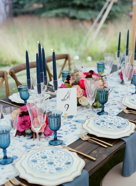Tablescape with Blue Patterned Plates and Table Runner, Gold Accents, Tall Blue Candlesticks and Pink Flowers