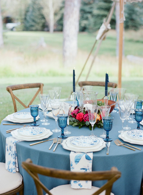 Round Table with Blue Tablecloth, Patterned Blue Napkins and Plates and Blue Glasses