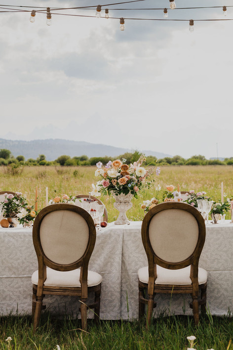 Romantic Table Set in a Field with Flower Arrangments in a Dramatic Flower Arrangement in the center of Two Chairs